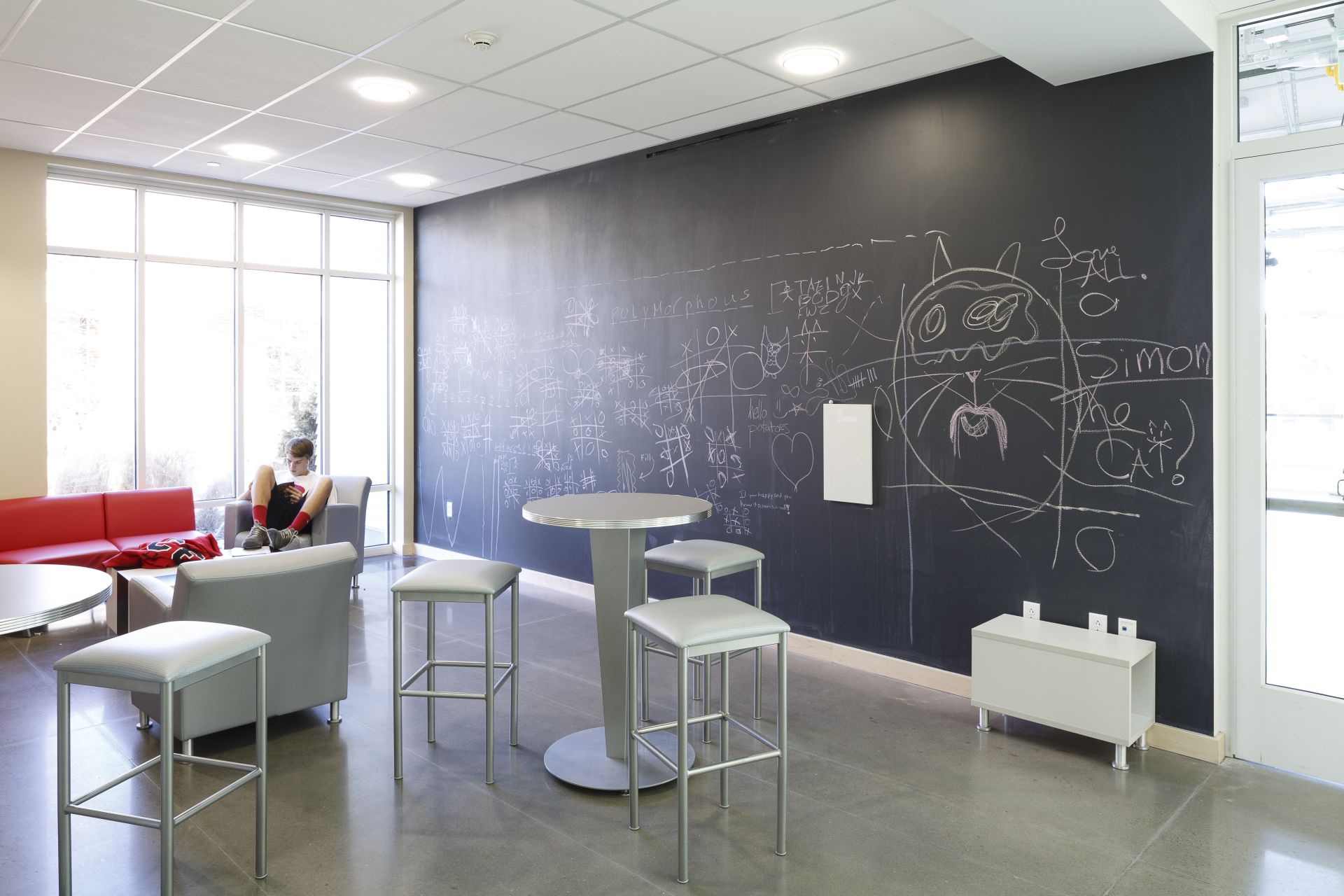 A chalkboard wall in one of the many collaborative spaces in the new building invites students to express themselves.