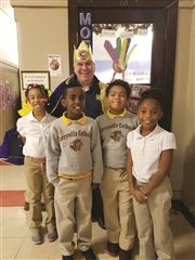 "Brother Ron Luksic poses for a photos with students from Corryville Catholic where he wears his ""King for Day"" crown made by the students."