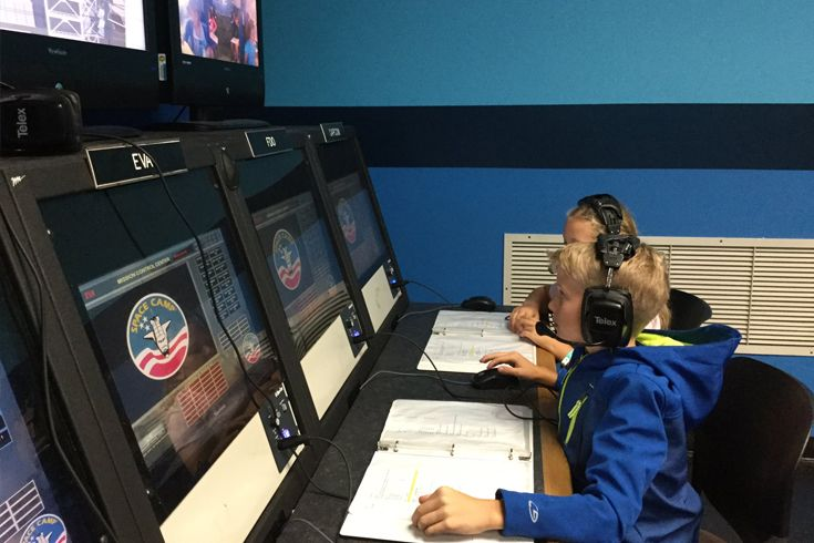 Grade 4 students man mission control during a simulation.