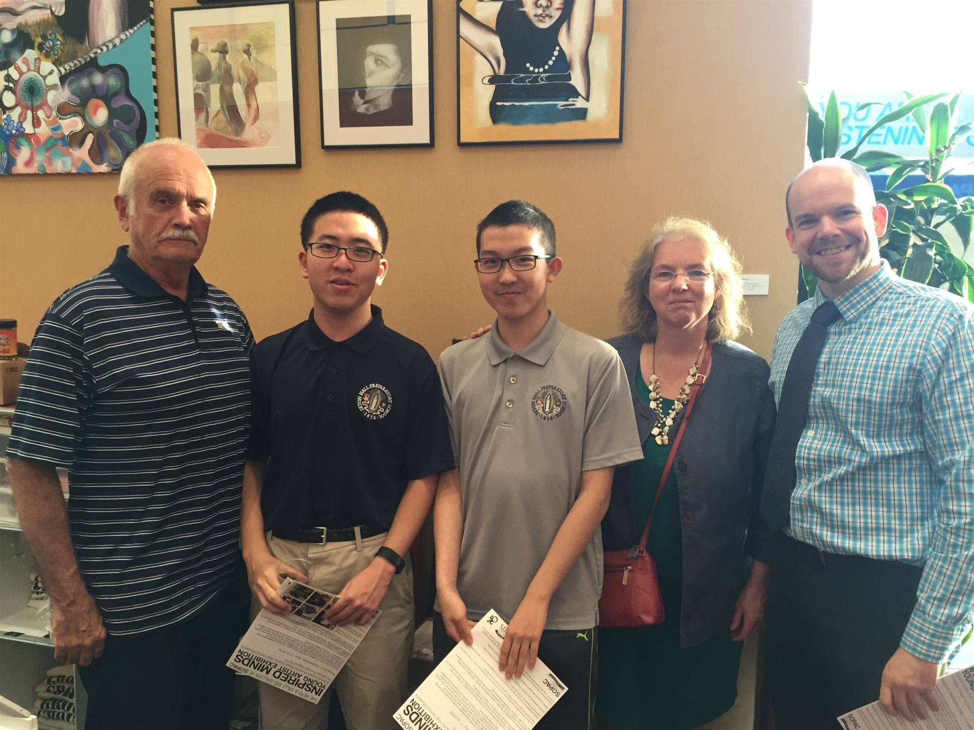 Host parents Vinnie and Liz McMahon and International Program Coordinator Michael Hegedus pose with Wenzhe Teng and Yuheng Chen under Yuheng's artwork at the South Orange Performing Arts Center.