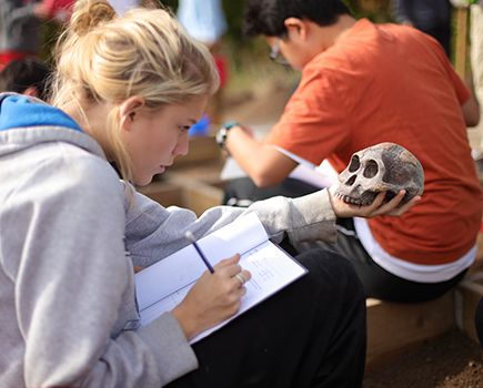 An LCS student takes down notes about an object found during the archeological dig on campus