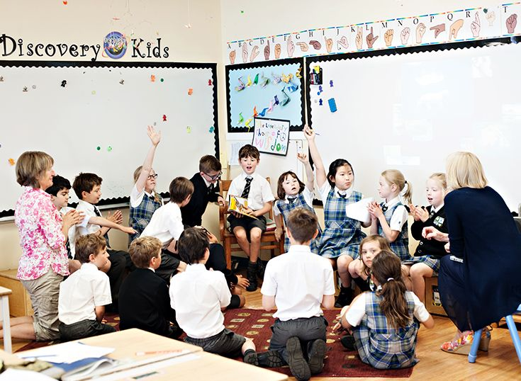 Group of children in private school sitting on floor learning