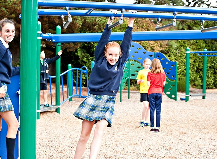 Girl hanging form monkey bars