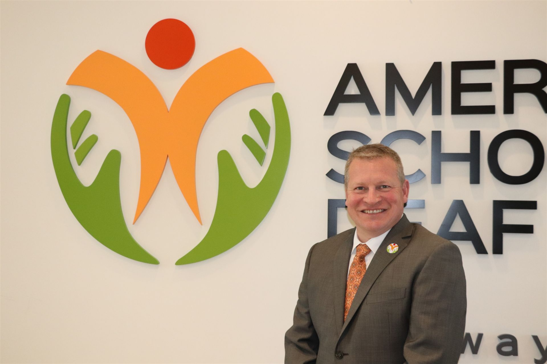 Jeff Bravin Stands in front of the ASD Logo