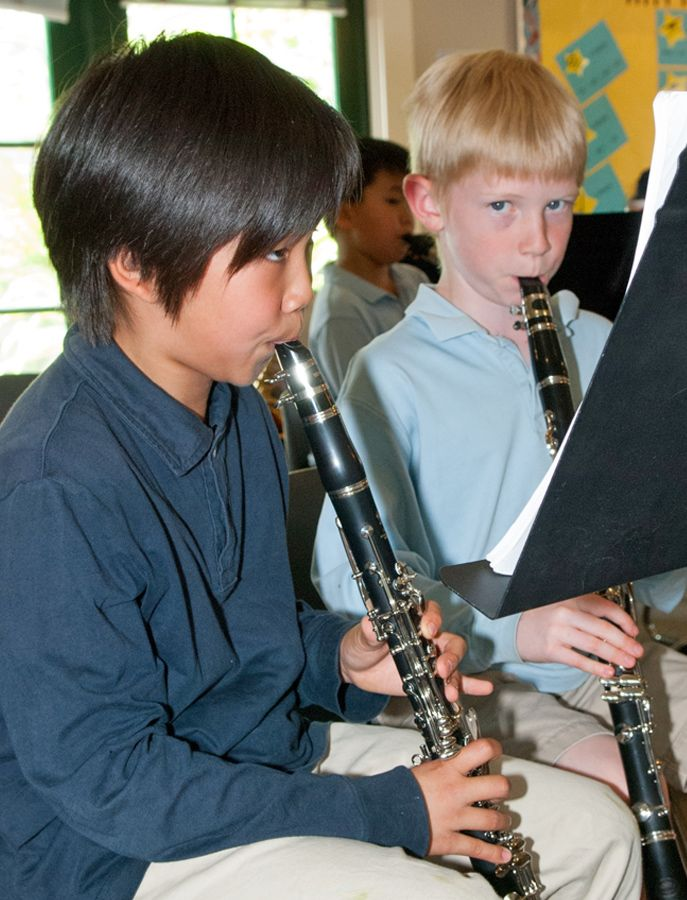 Students learn their parts in a musical piece in the classroom.