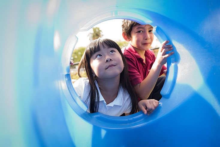 Boy and girl looking into a playground tube