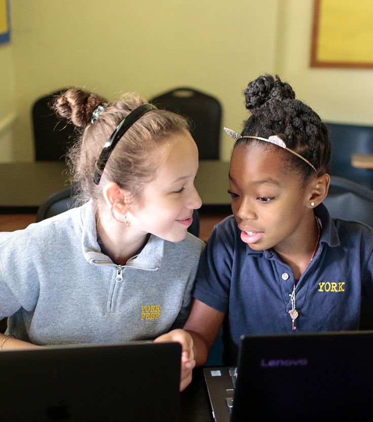 Two middle school students working on laptops at York Prep School in NYC working on computers.