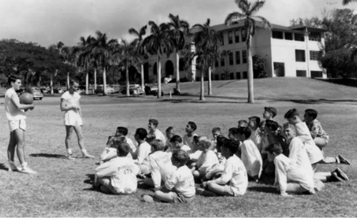 In addition to their classroom duties, sixth-grade teachers Bill Knowlton and Tom Metcalf lead a physical education class on lower field. (Photo: Punahou Archives c. 1950)