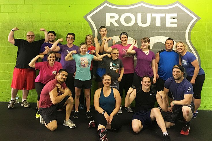 Group of people in workout gear flexing their muscles