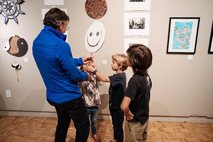 Male holding up an artistic smiley face to children in an art gallery