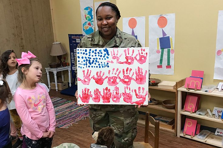 Solider mother holding a photo of hand painted flag