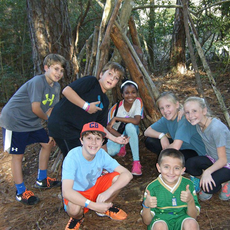Fifth graders at Camp Allen gather natural resources to construct an outdoor shelter. Warning: if it