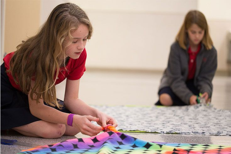 Not only do students learn a lot about the Old and New Testaments; Bible class is also a forum for honoring God by serving others. Here sixth graders make blankets for patients at Texas Children's Hospital.