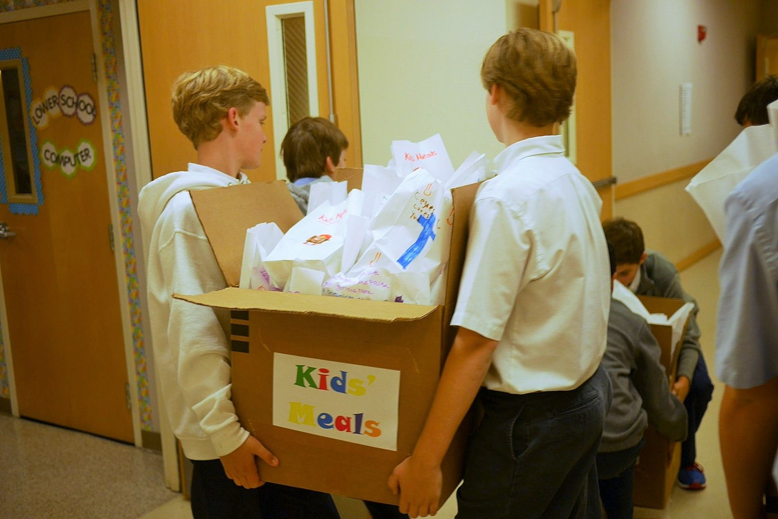 Shared service projects like making sack lunches for Kids Meals adds depth to the relationship between buddies.