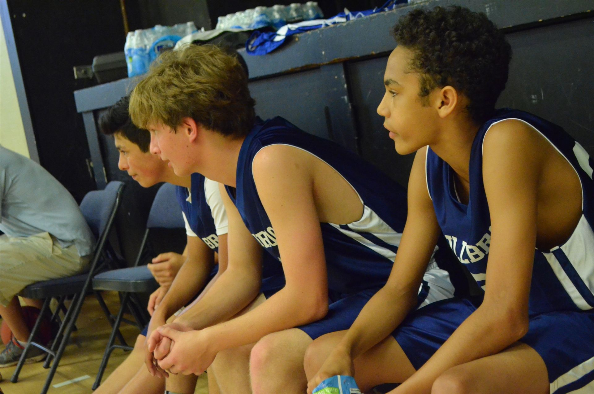 Our current 8th grade team watches the on-court action from the bench!