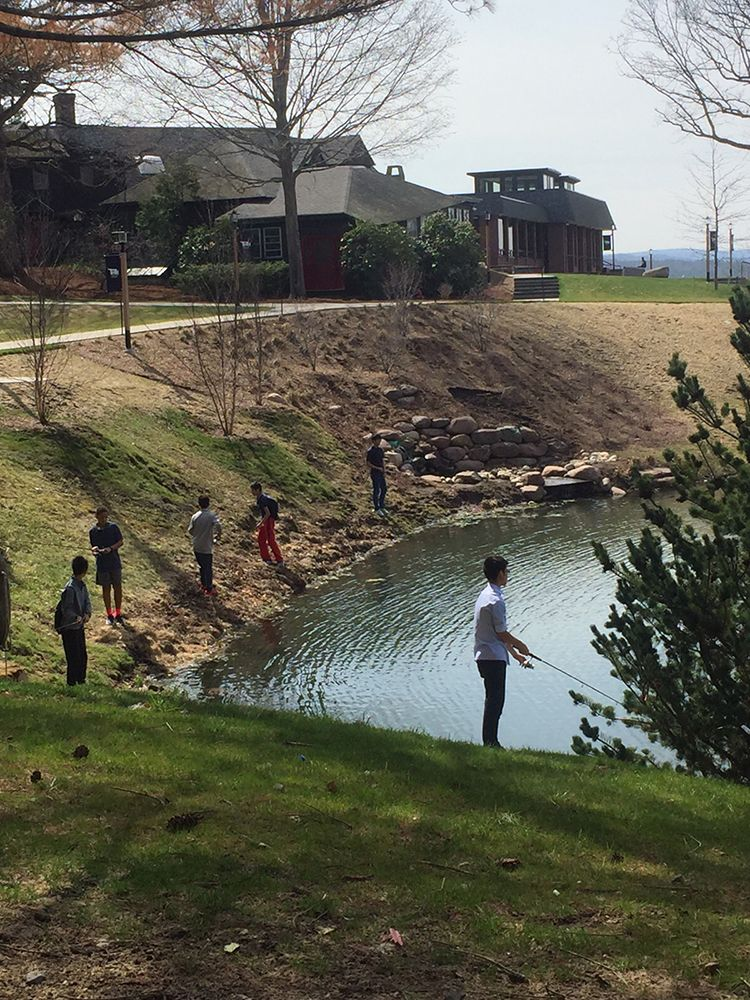 Students fishing around Whipple Pond in the center of the Eaglebrook campus