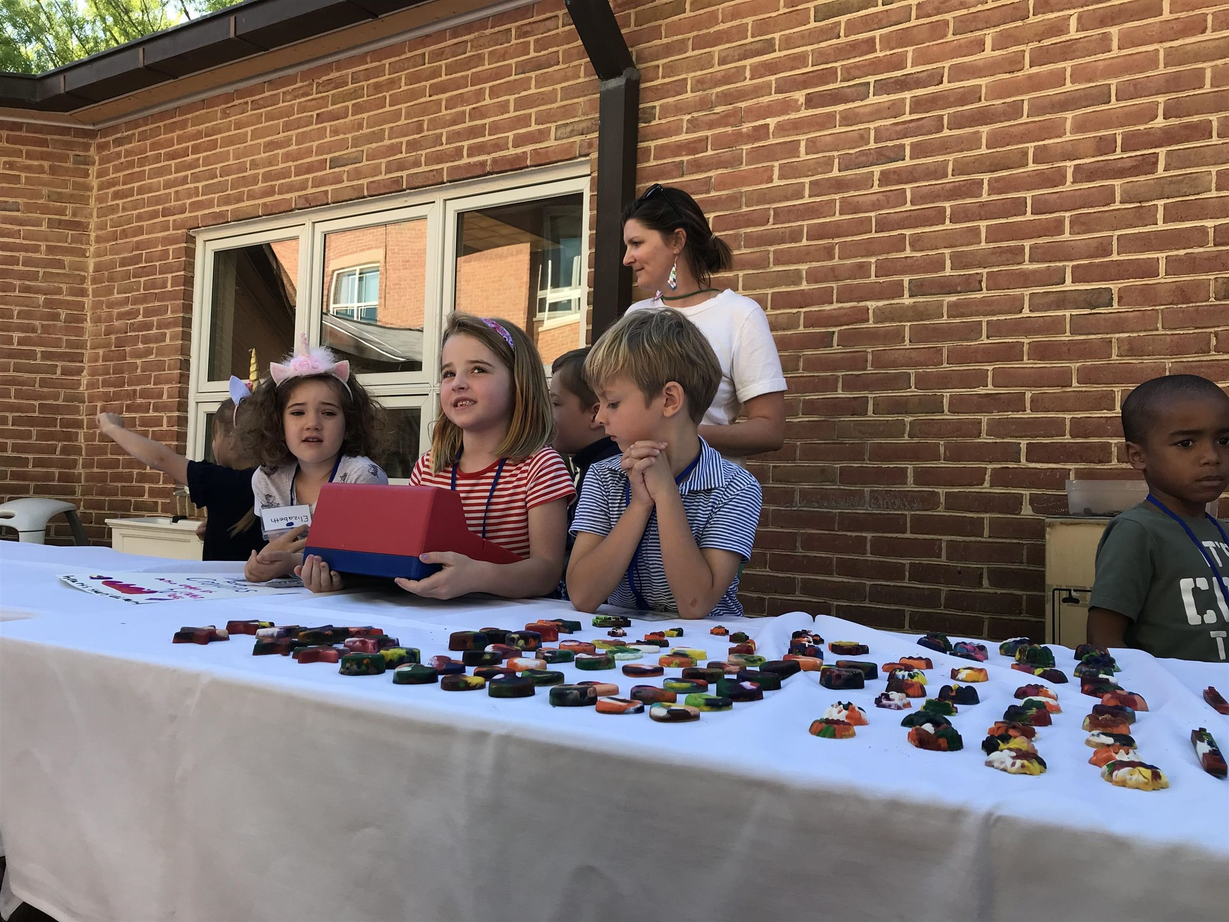 At the annual Kindergarten flea market, students take turns buying and selling items they have crafted, such as wool bracelets, shaped crayons, bird feeders, and more.