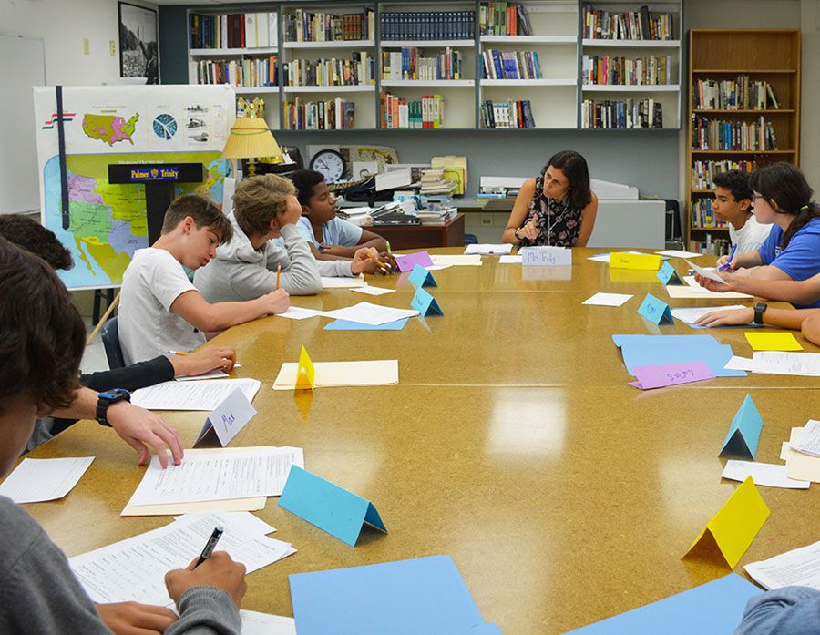 Falcon Summer Camp participants sitting around a table listening to an instructor and working on assignemnts