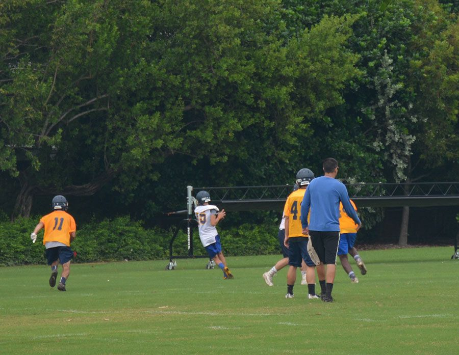 Players in football uniforms  outside on the Palmer Trinity School football field playing during the Falcons Summer Camp Football Conidtioning Clinic
