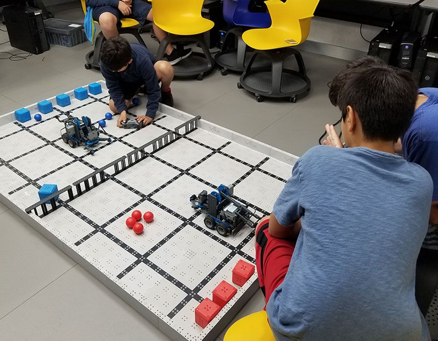 Falcon Summer Camp participants working with robots they built in the Robotics Camp