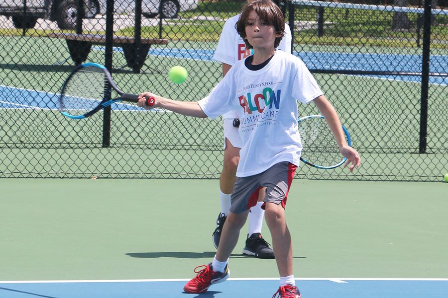 Falcon Summer Camp participant playing swing a tennis racket on the tennis court.