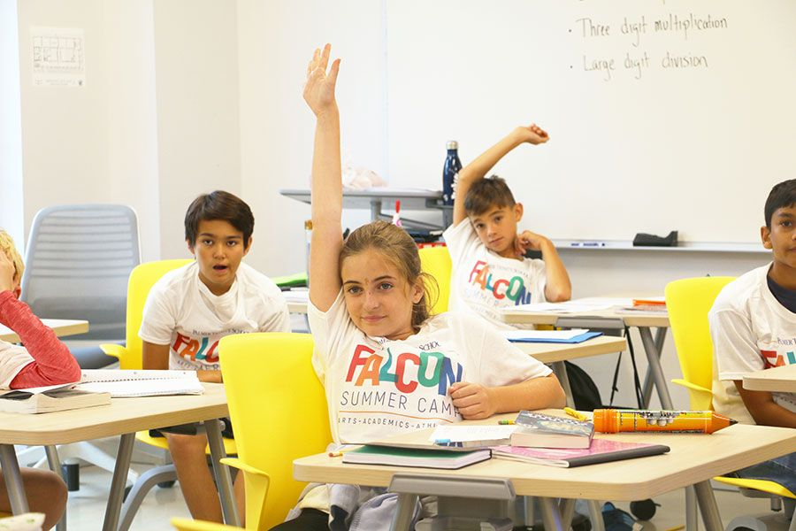 Young male and female Falcon Summer Camp participants sitting sitting in a classroom taking part in class discussion. One female student is raising her hand.