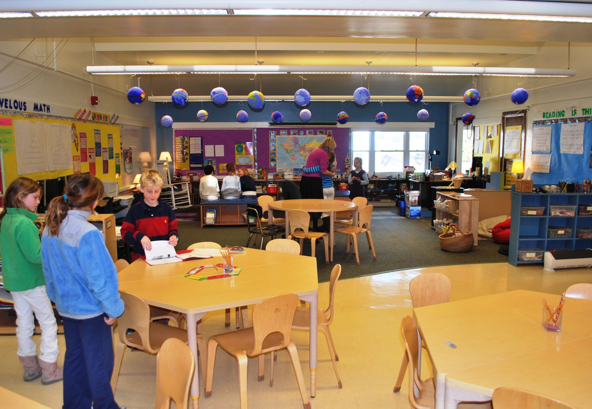 Renovated between 2002 and 2006, bright, child-friendly classrooms open inside to a central commons area and outside to various play areas connecting children to each other and to nature.