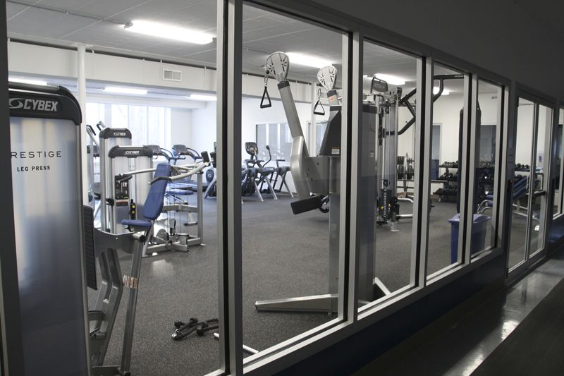 The New Fitness Center (approx. 1600 sq/ft) is made up of two individual rooms to meet the unique needs of the community. The first, a multi-purpose space for classes, such as yoga, fits 20 students comfortably. The space includes a cork floor, physioballs for core exercises, mats to stretch, and a wall mount for three TRX suspension trainers. The other part of the Fitness Center, dedicated to strength training equipment, includes more than 10 Cybex machines, ranging from treadmills and arch trainers to a rower and virtual-reality spin bikes. Many of the machines also include televisions with cable. In addition, a motion cage combines a trainer, rebounder, punching bag, and bench press in one machine. The Center was designed with large energy efficient windows as well as LED lighting.