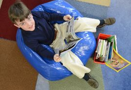 A student looks up from his book while reading in a bean bag chair.