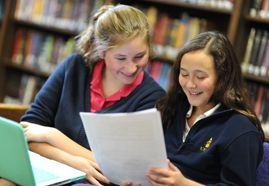 Two students smile while reading a piece of paper.