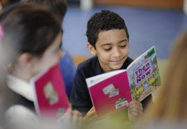 A young student smiles while reading an illustrated book.