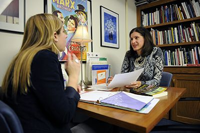 A student meets with a college guidance counselor to discuss their college plans.