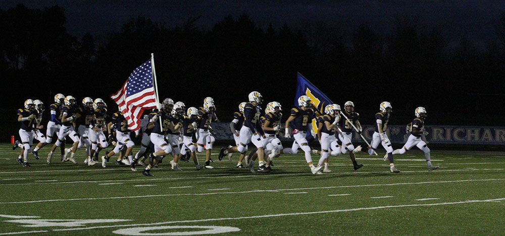 Football players run onto the field with the United States flag and a USM Wildcats flag.