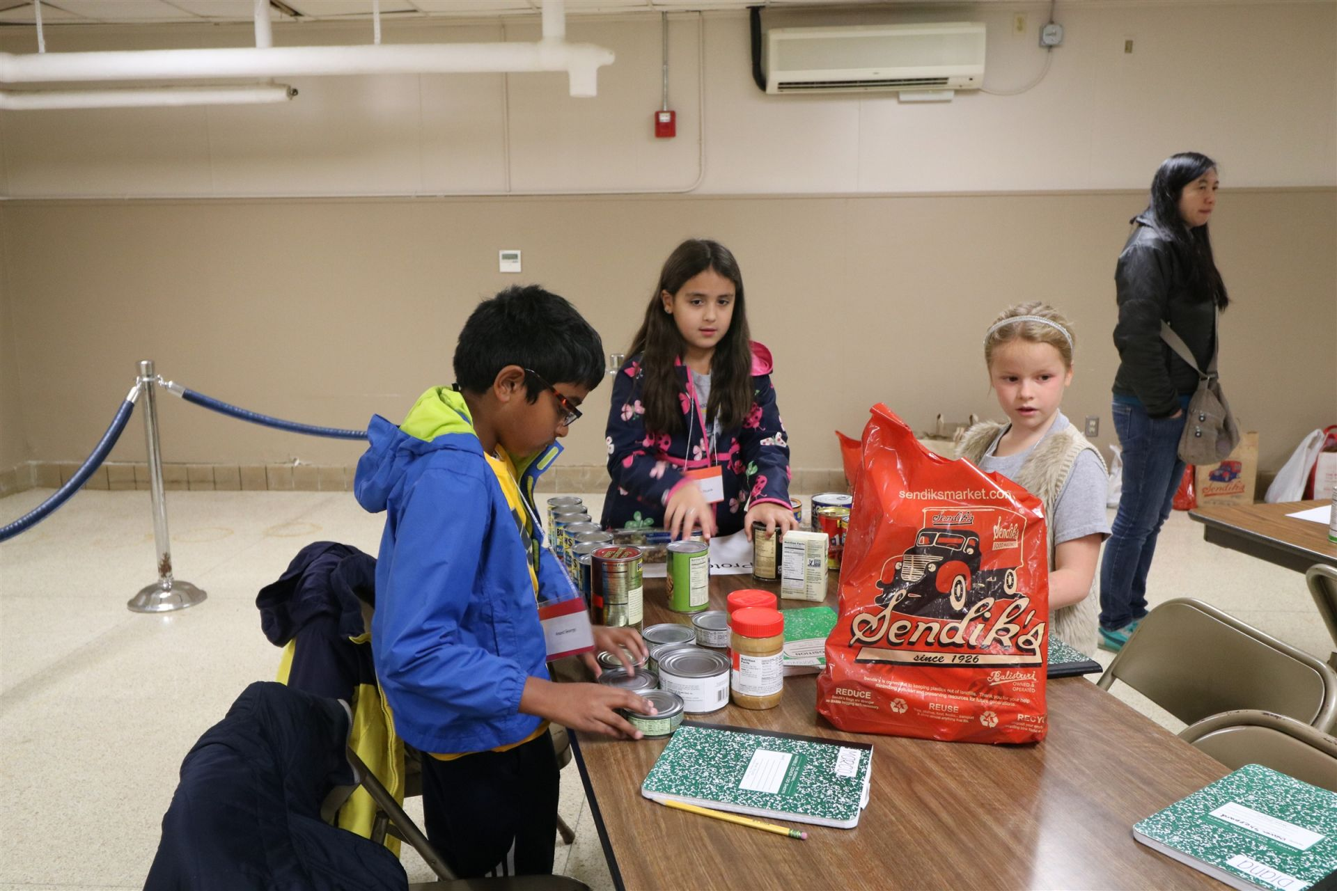 Students fill bags with food at the Riverwest Food Pantry.