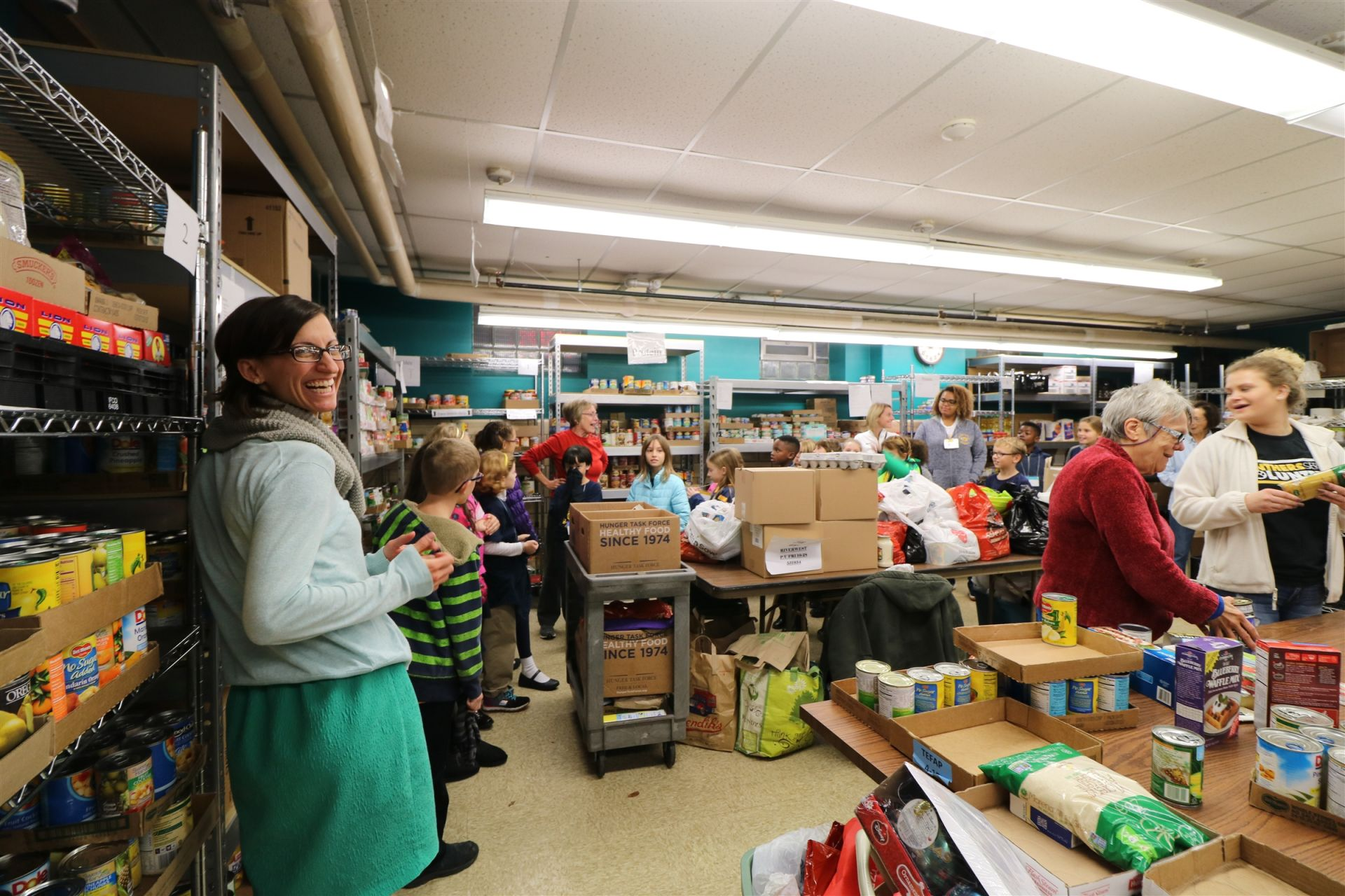 A teacher smiles for a photo during a field trip to the Riverwest Food Pantry.