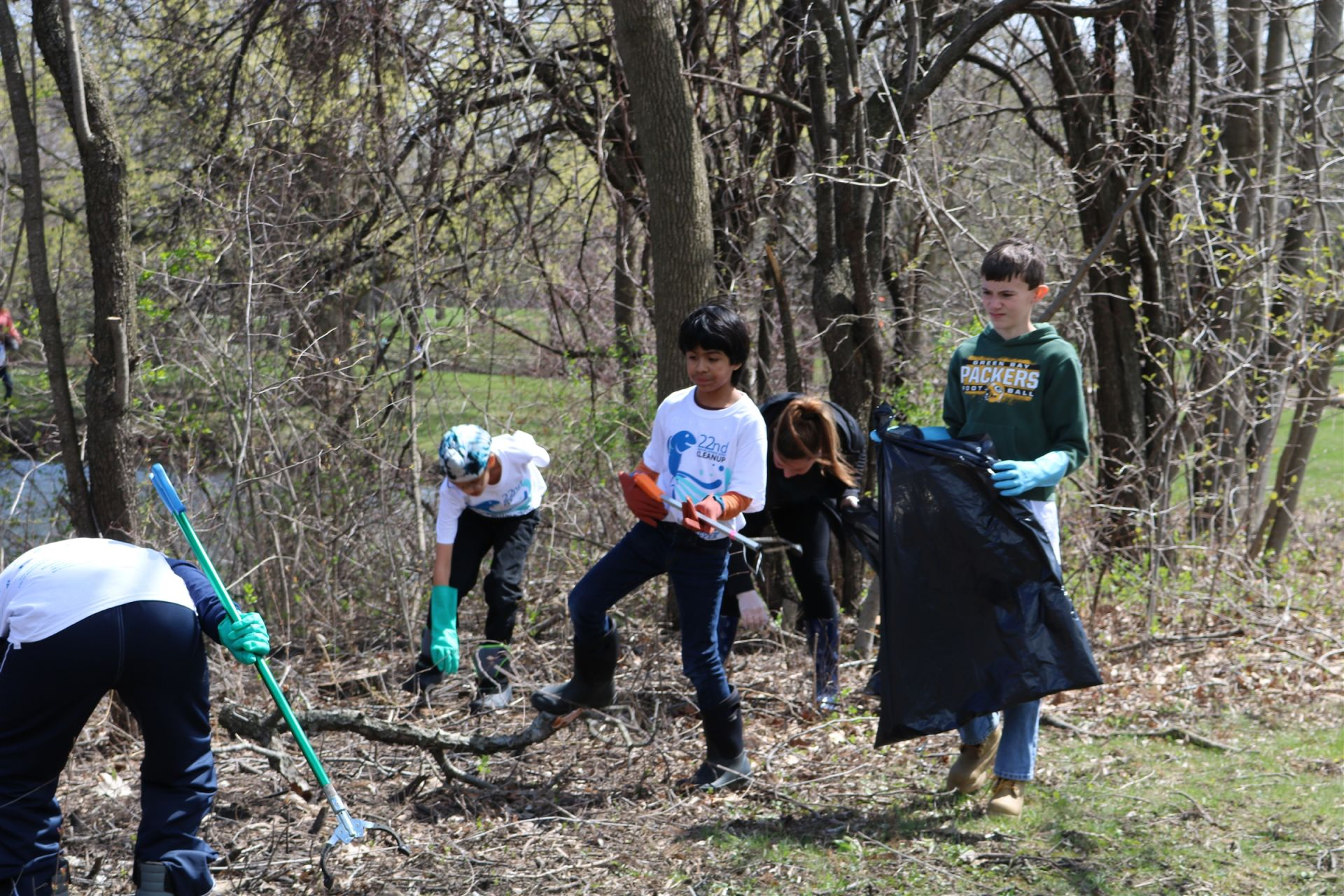 Students collect trash in large bags during a river cleanup trip.