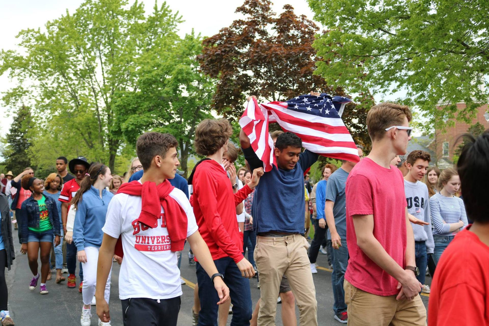 Students drape the American flag over their shoulders during the March to the Memorials celebration.