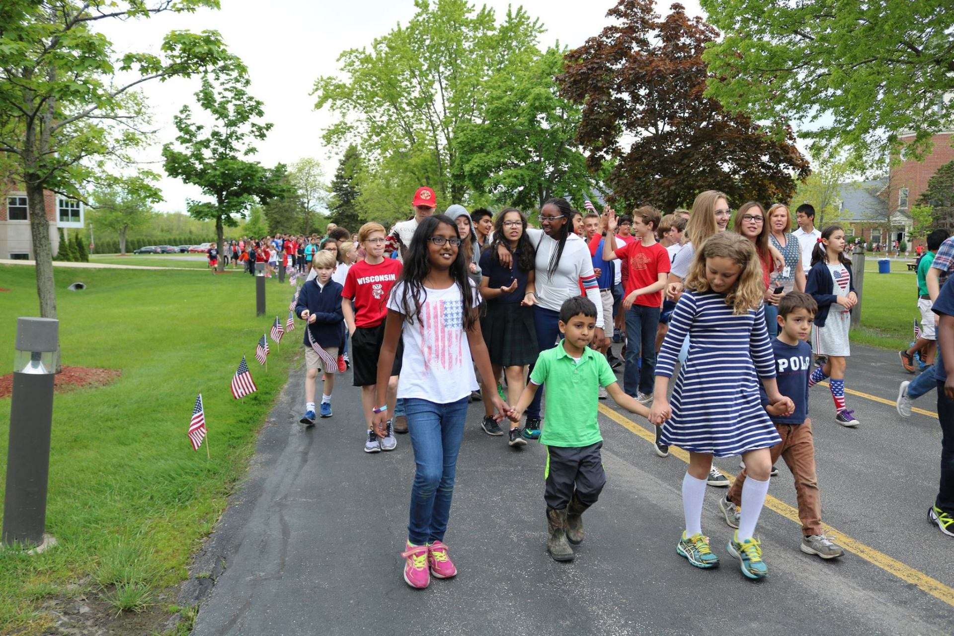 Students hold hands as they march through campus during the March to the Memorials celebration.