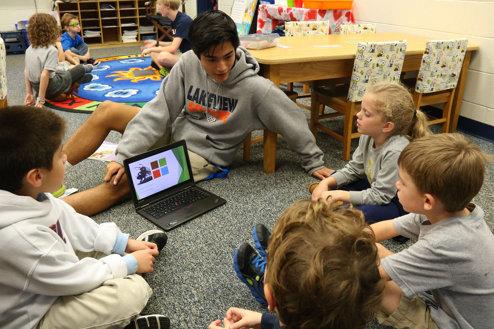 Using his laptop, an AP Spanish student reads a story in Spanish to Kindergarten students.