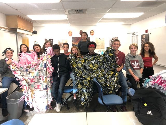 Upper school students making blankets to donate to Camp Harmony.