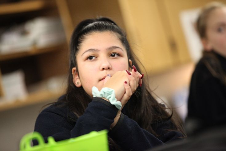 A girl student at Trinity School of Midland is listening to her teacher.