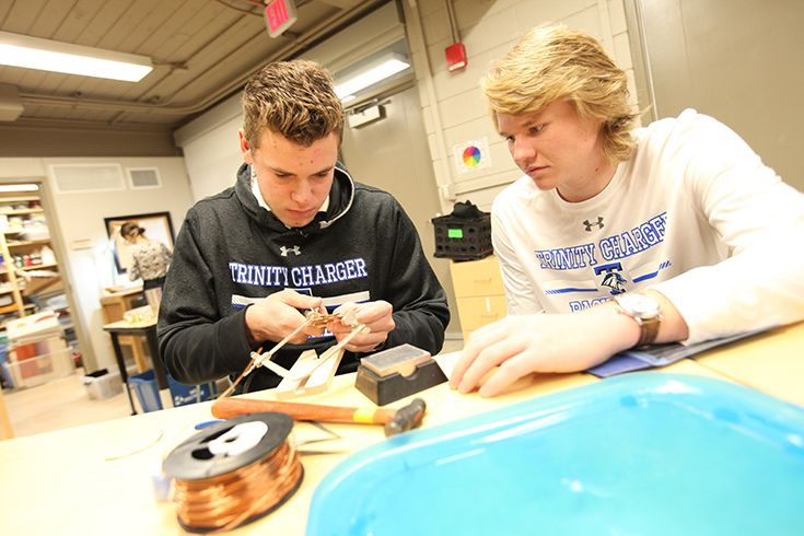 Two high school Trinity School of Midland students working on a science project together.