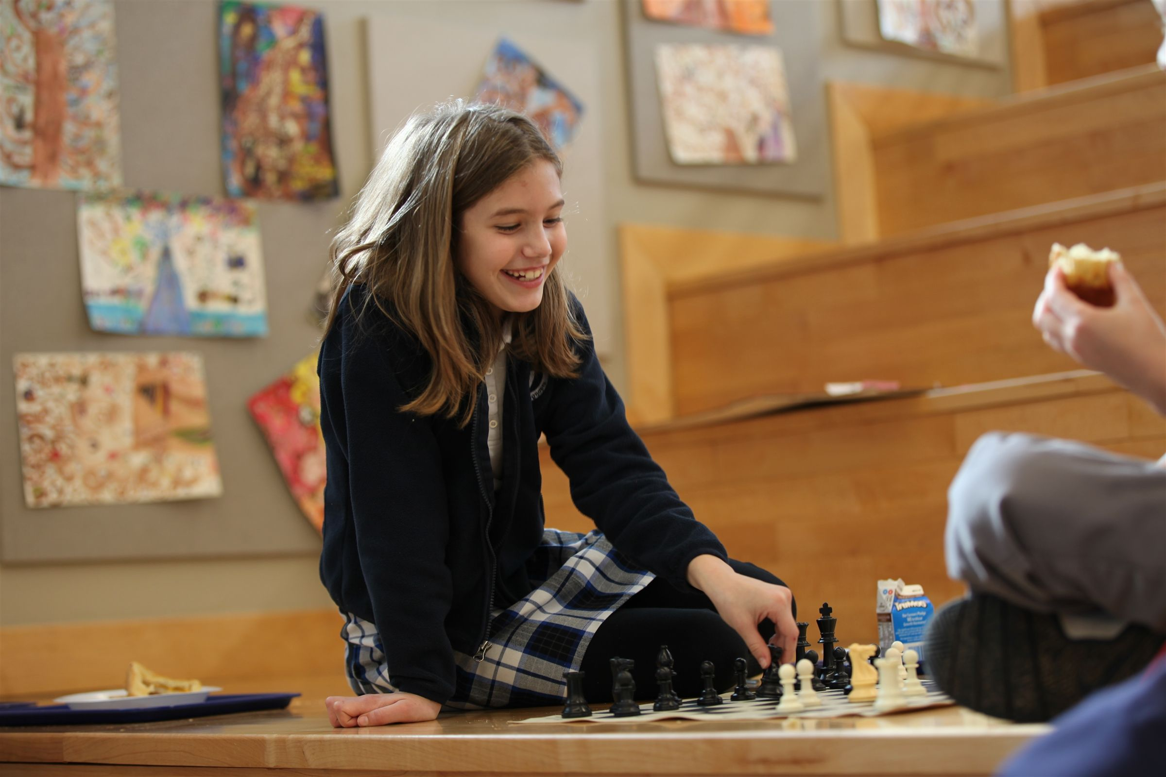 Girl sits on the stairs at Trinity School of Midland plays chess with another student.