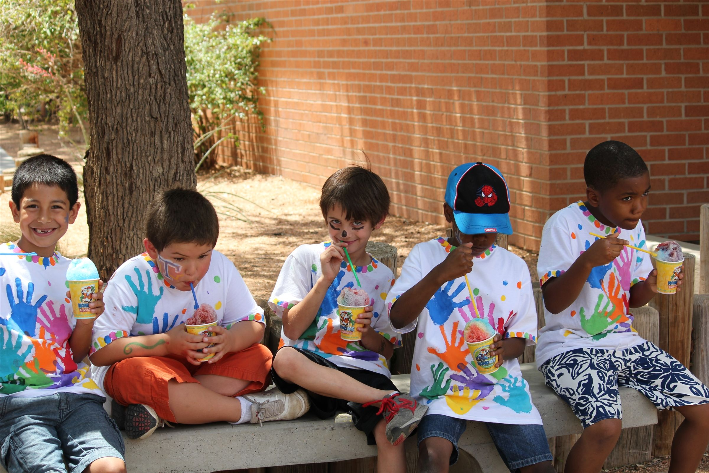 Trinity School of Midland students sit on the sidewalk with painted t-shirts after field day.