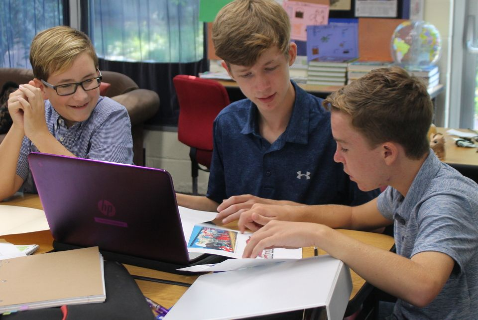 Three students working together on laptop.