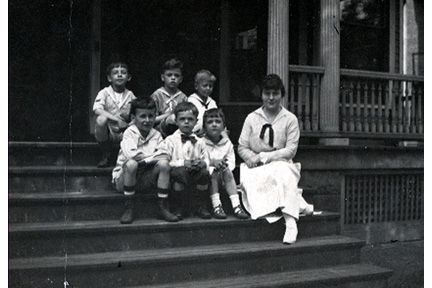 1588 Ansel Road. Miss Rowland (1918-1921) and six boys on steps.