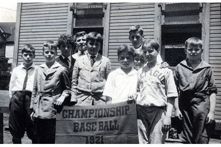 Group of student athletes with 'Championship baseball 1921' banner. Possibly Hawken's first championship. Wally Wallace is right rear, the tallest.