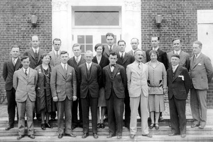 Outside front entrance Bolton Hall, Lyndhurst, 1928. Nineteen are present; the list of faculty has 21 names: John Carney [headmaster] (fourth from left, front row), Robert Adams, Mrs. Robert Adams, William Baker, Mr. Robert Brewer, Mrs. Robert Brewer, Seward Covert, Guy Christian, Florian Heiser, Thayer Horton, Maurice Howard, Miss Lucretia Jones, Miss Anita Jopling, Miss Fannie Luehrs, Ross MacMahon, John McCarthy (far right, back row), Joseph Motto, Ralph Patch, Elmer Sipple, Mortimer Smeed, Charles R. Stephens.