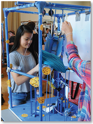 Students build Rube Goldberg machines — intentionally complex devices that accomplish a simple task such as watering a plant, popping a balloon, ringing a doorbell, or answering a cell phone.