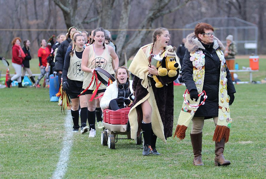 . . .followed by the Hounds, led by Houndbacker Patty Boswell and Hound Captain Haley B. '19, pulling a wagon with Manager Holland D. '19 who was injured.